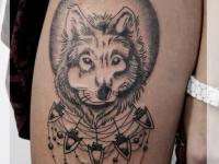 Татуировка голова волка на бедре