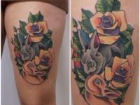 Татуировка кролики в розах на бедре