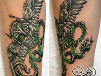 Татуировка в виде железной совы на предплечье