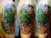 Татуировка голова дракона на плече