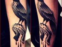 Татуировка птица с челюстью на предплечье