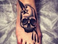 Татуировка череп с кинжалом на ступне