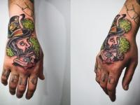 Татуировка голова в шляпе на кисти руки