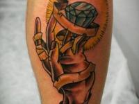 Татуировка рука и алмаз на икре