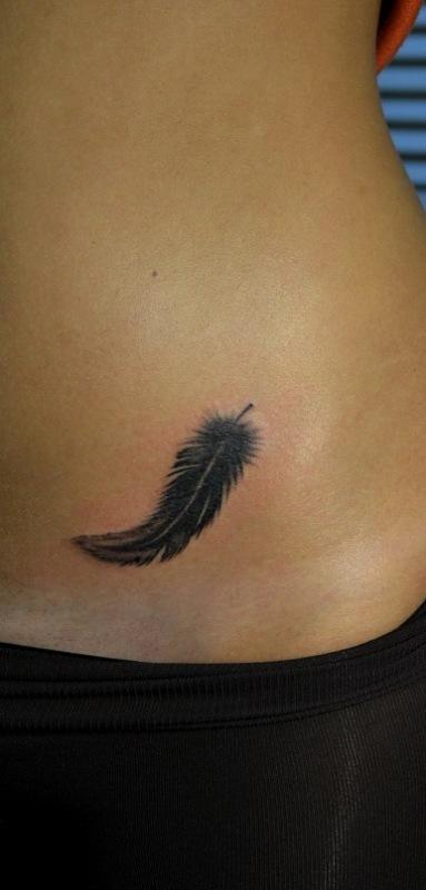Татуировка перышко на животе