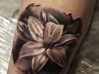 Татуировка распустившейся лилии на руке