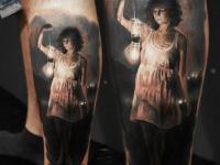 Татуировка девушки с фонарем на ноге