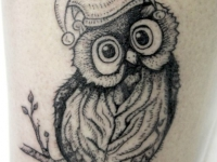Татуировка филина в шутовской шляпе на руке