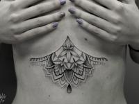 Татуировка в виде ожерелья из цветков под грудью
