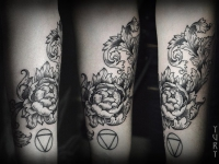 Татуировка цветка и знак стихии воды на руке