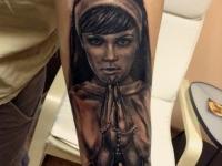 Татуировка красивой девушке во время молитвы на руке