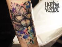 Татуировка цветок с элементами цветных клякс на предплечье