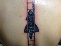 Татуировка девушка поднимающаяся вверх по лестнице на спине