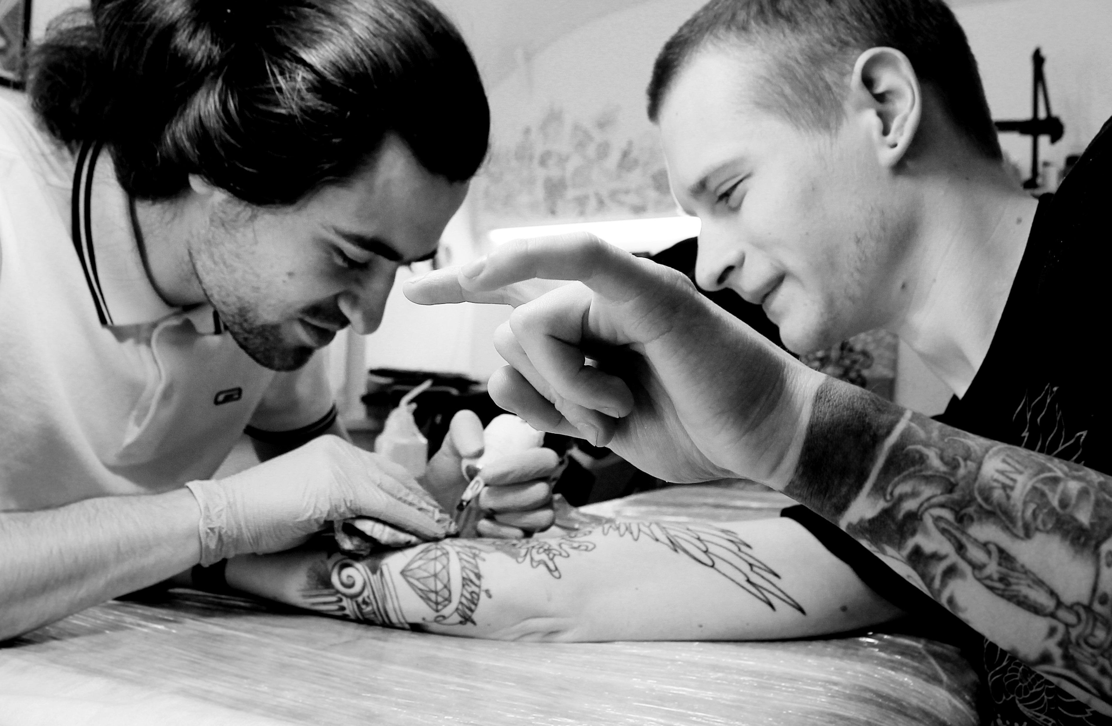 Мастер Саша Новик трудится над новой татуировкой мастера Валеры Моргунова.