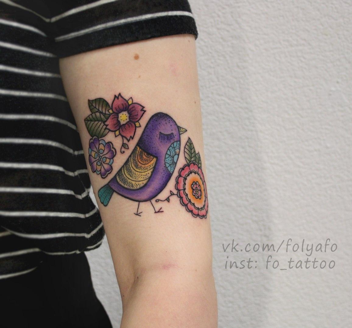 Птичка с цветами расположена на руке. Цветная татуировка.